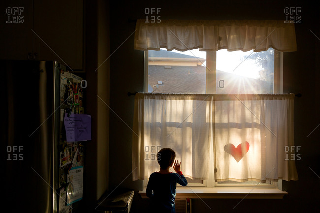 Silhouette of a boy standing in front of a kitchen window