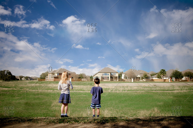 Boy and a girl standing in a field looking at a row of houses in the distance