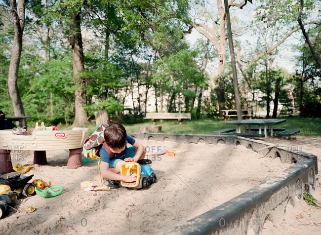 Boy playing in a sandbox at a park