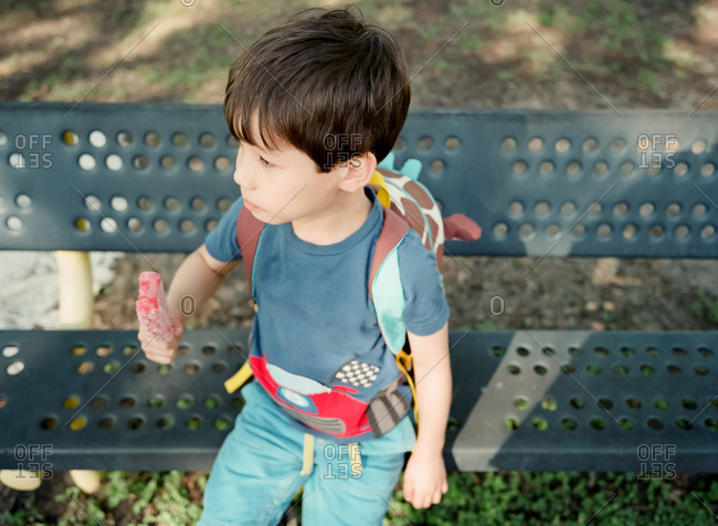 Boy wearing a backpack, sitting on a park bench, eating an ice cream bar