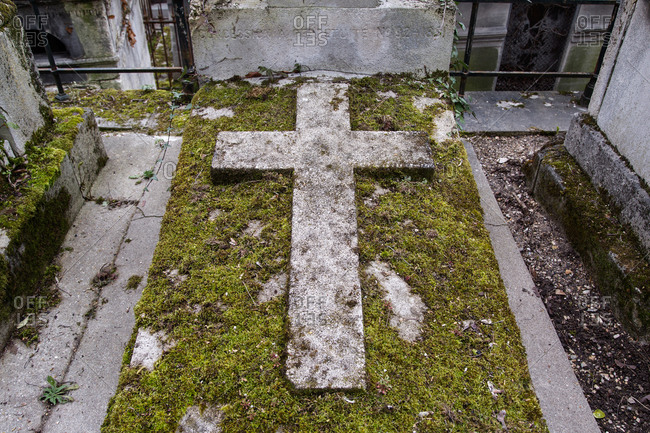 Close up of a cross on the grave at Pere Lachaise Cemetery