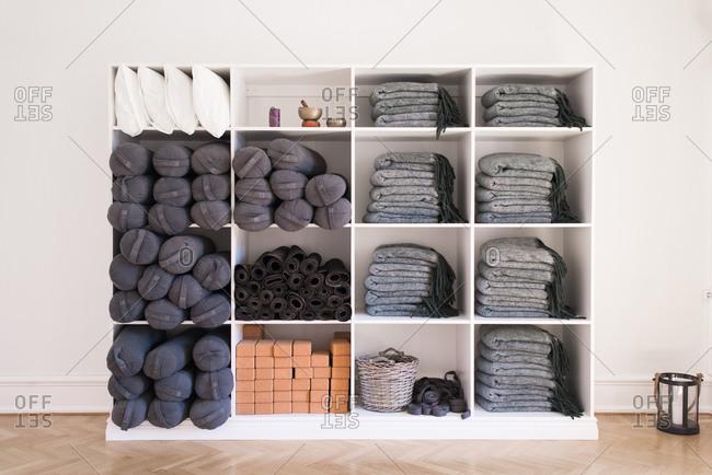 Shelves of mats, blocks and bolsters in yoga studio