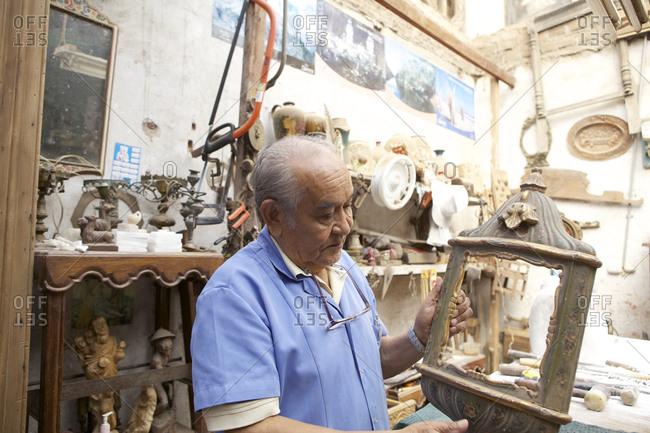 Peru - April 2, 2013: Antique vendor holding an ornate wooden frame