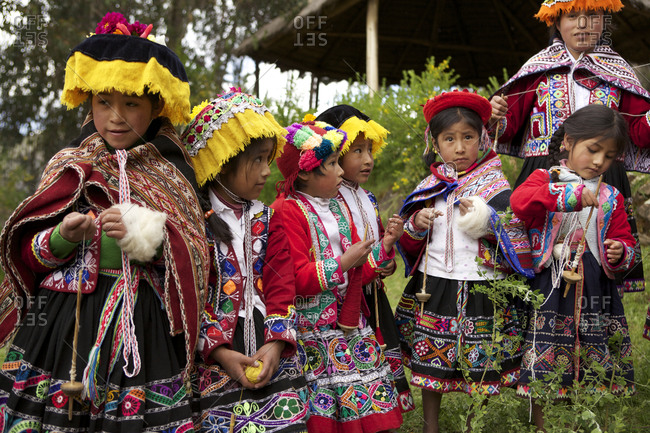 Peru - April 5, 2013: Young children participate in the Amaru tradition of spinning yarn from wool
