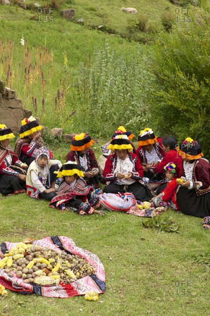 Peru - April 5, 2013: Amaru people eating community meal sitting on grass