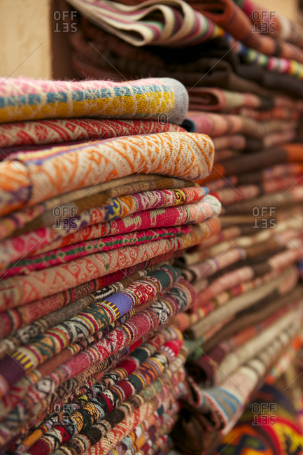 Stacks of brightly colored woven textiles at Pisac Market, Cusco, Peru