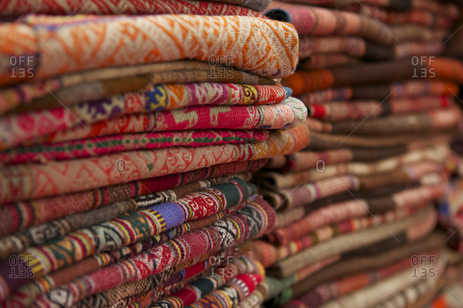 Stacks of folded woven textiles at Pisac Market, Cusco, Peru