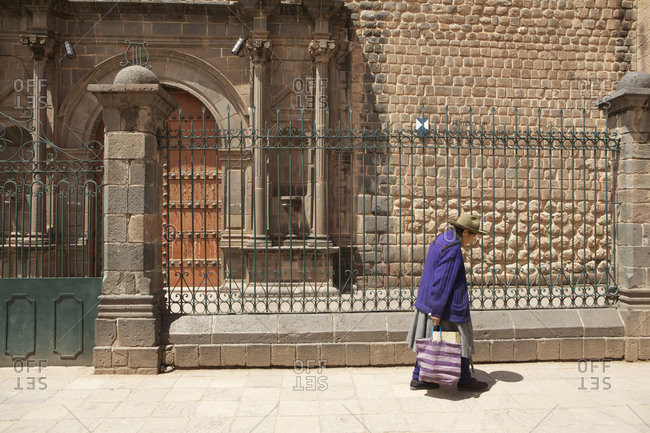 Peru - April 7, 2013: Elderly woman walking past Santa Clara de Asis Temple, Cusco, Peru