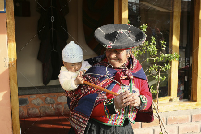 Peru - April 4, 2013: Woman with baby on her back in the Chinchero community  in Peru