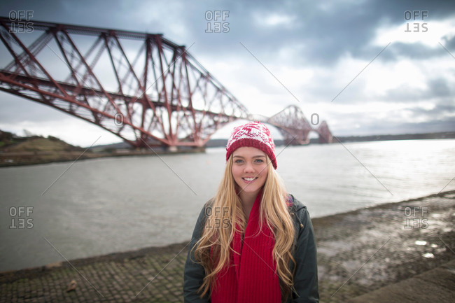 A young woman poses in front of the Forth Rail Bridge in Queensferry, near Edinburgh, Scotland