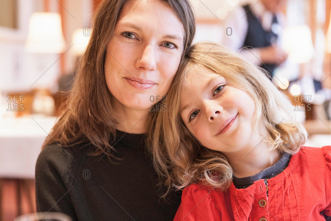 Portrait of mid adult woman and daughter in restaurant