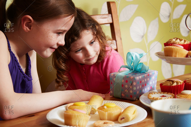 Two girls looking at birthday present with plate of cakes
