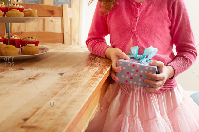 Girl holding birthday present, mid section