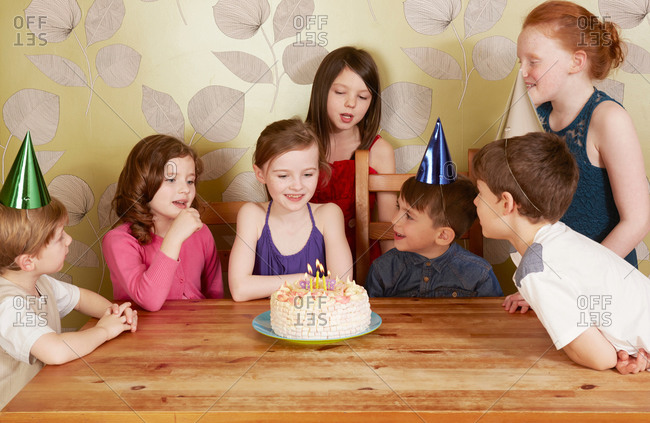 Children at birthday party, girl with cake