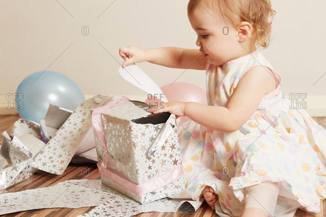 Toddler girl opening birthday present