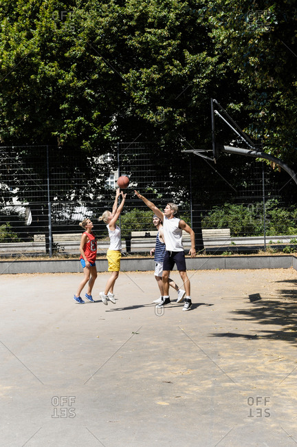 Group of friends playing basketball on court in park