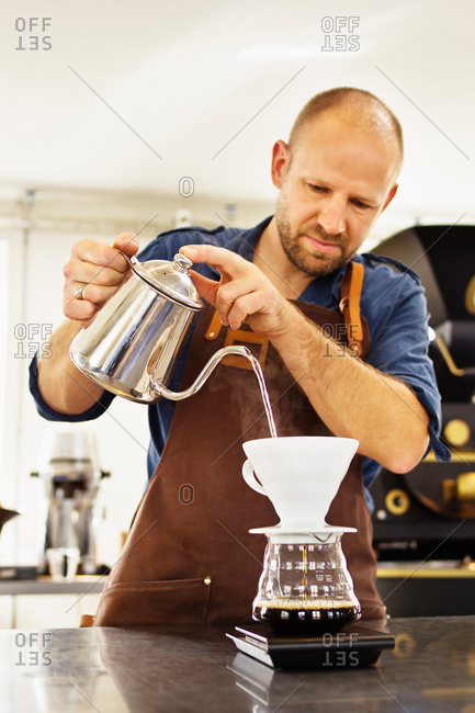Barista pouring boiling water into coffee filter
