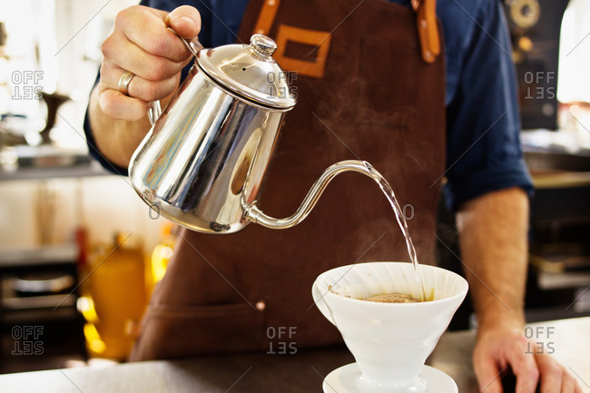 Close up of barista pouring boiling water into coffee filter