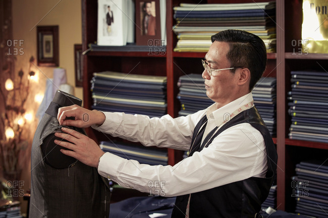 Tailor pinning garment on tailors dummy in shop