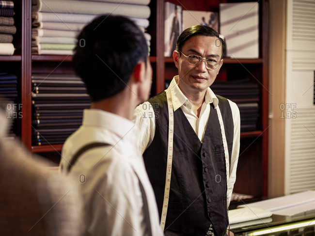 Father talking to son in family tailoring business