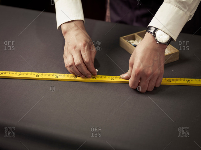 Tailor chalking measurements on table in traditional tailors shop