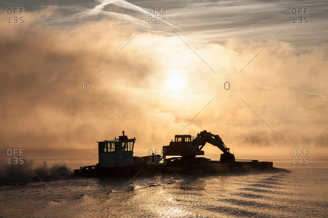 Silhouette of excavator on barge,  Lake Maggiore, Stresa, Piemonte, Italy