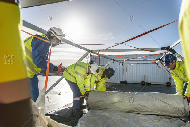 Emergency Response Team workers unrolling tarp for a tent control center