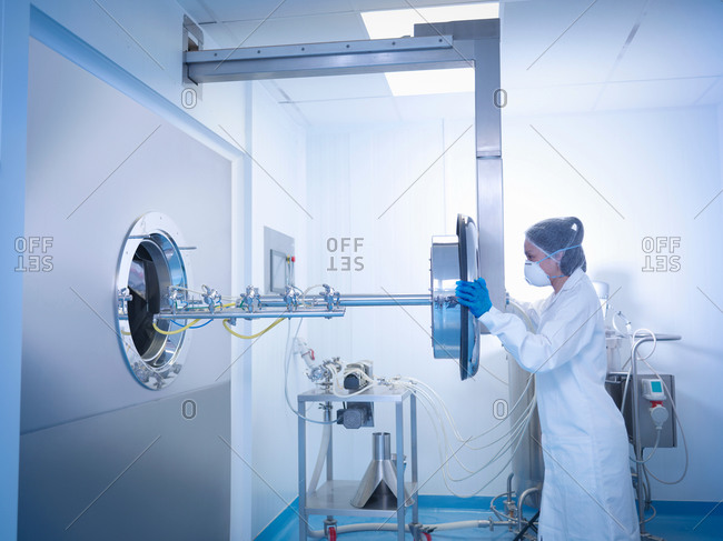 Worker inserting spray jets into tablet coating machine in pharmaceutical factory