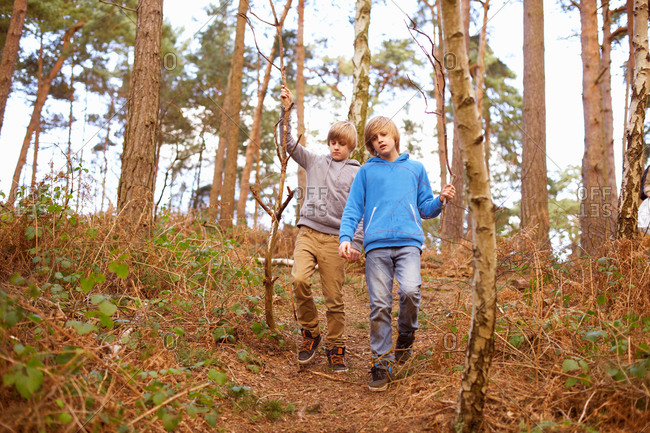 Twin brothers strolling in woods