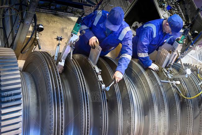 Engineers fitting blades to steam turbine in turbine repair bay