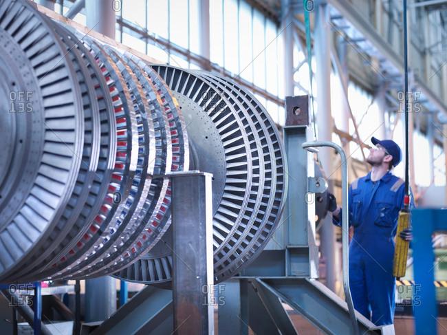 Engineer lifting high pressure steam turbine with crane in workshop