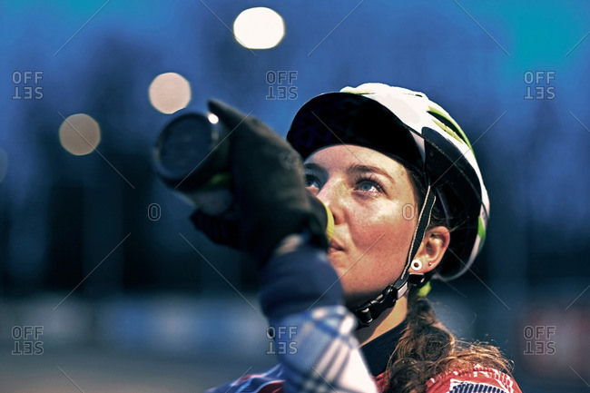 Close up of female cyclist drinking from water bottle