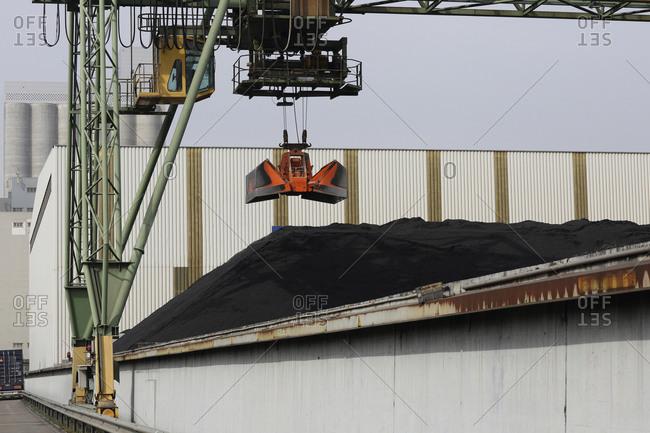 Crane grab and pile of coal in port