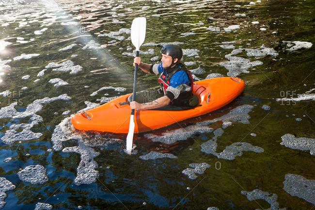 Mid adult man kayaking on peaceful river