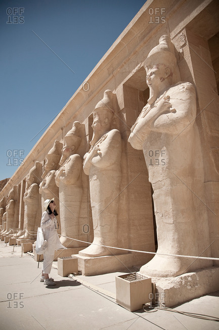Woman looking at statues at the Mortuary Temple of Queen Hatshepsut, Egypt
