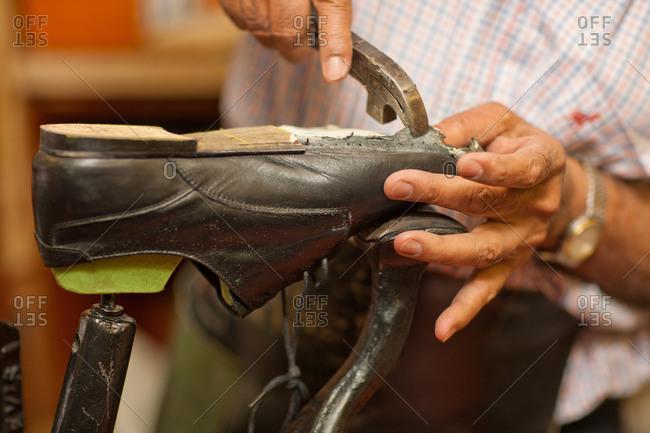 Cobbler mending sole of shoe
