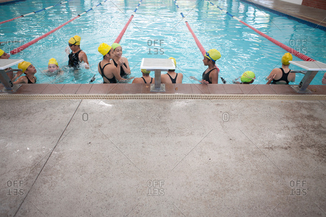 Group of schoolgirls taking a break in swimming pool