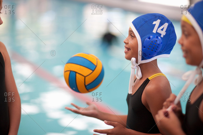 School girl water polo players poolside with ball
