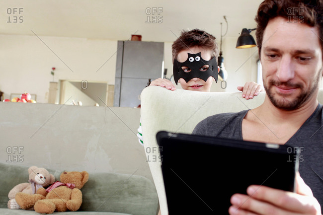 Masked son distracting father from digital tablet