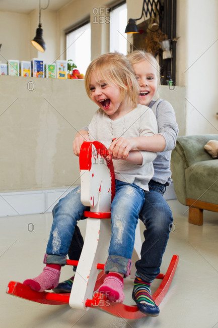 Two young sisters playing on rocking horse