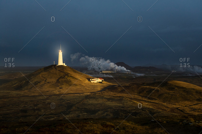 View of distant glowing lighthouse, Reykjanes, Iceland