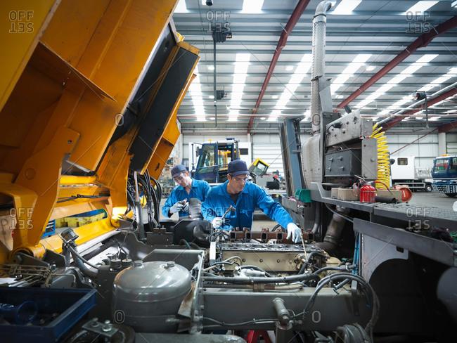 Halifax, United Kingdom - March 20, 2014: Engineers repairing engine in truck repair factory