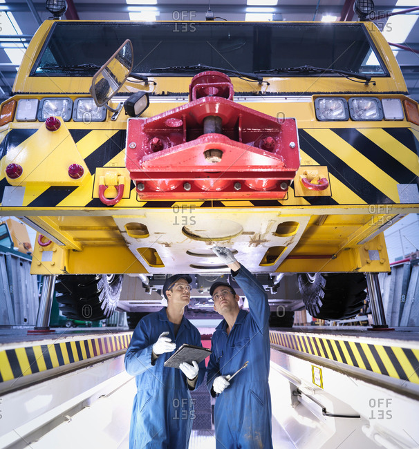 Halifax, United Kingdom - March 20, 2014: Engineers inspecting underneath truck in repair factory