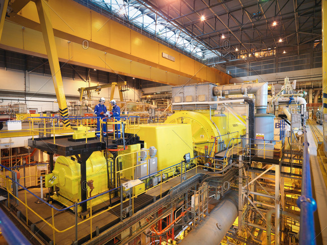 Two workers in turbine hall of power station
