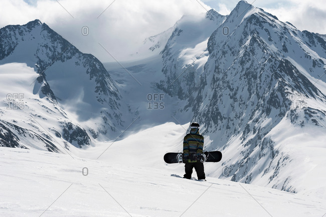 Young male snowboarder walking up mountain, Obergurgl, Austria