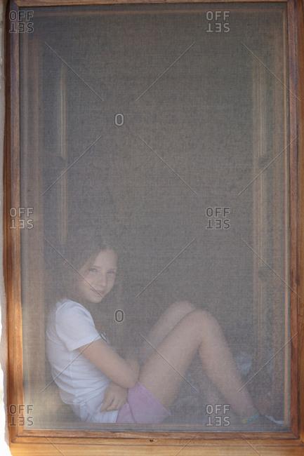 Portrait of girl sitting in obscured window frame