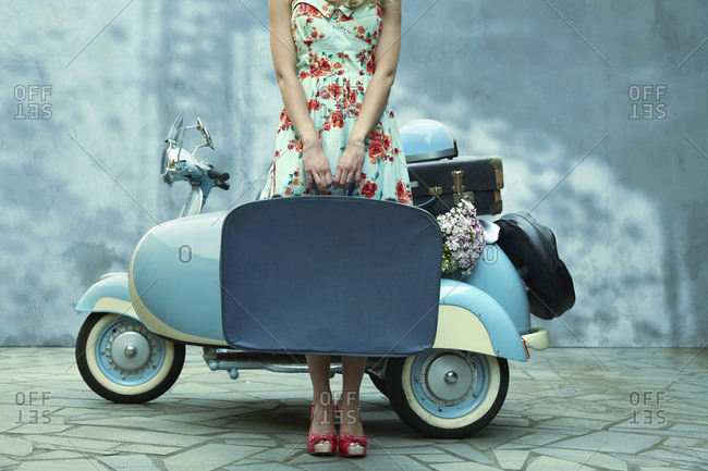Woman holding suitcase near vintage scooter
