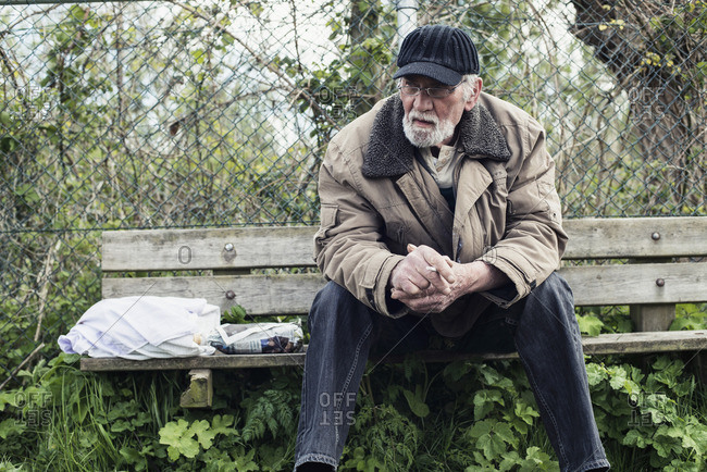 Bearded man smoking a cigarette on bench in park