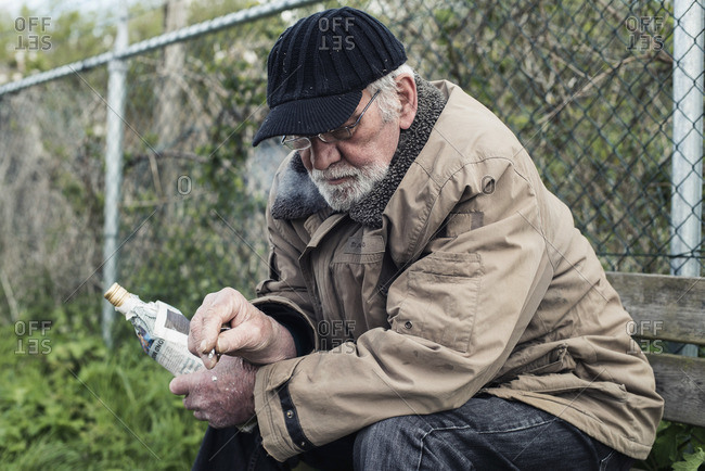 Senior homeless man on bench with cigarette and bottle