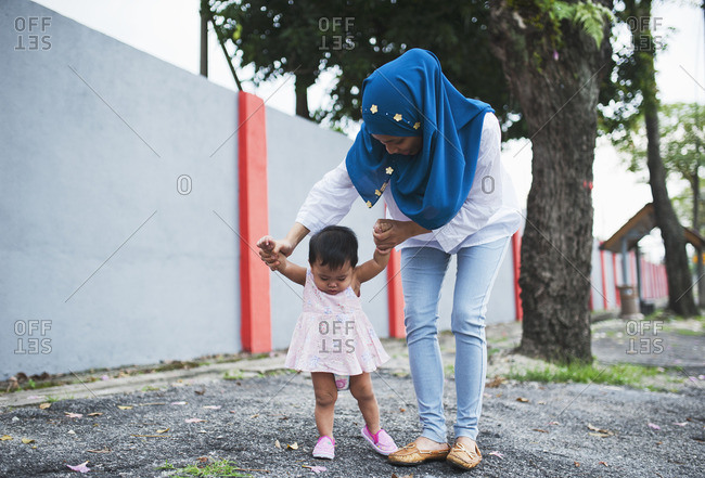 Woman holding hands of toddler girl on sidewalk